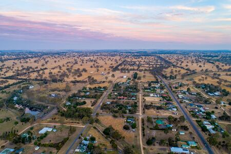 Aerial view of rural road passing through Australian countryside and small settlement at sunset