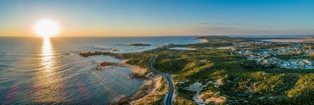 Scenic drive passing near ocean coastline and Beachport town at sunset - wide aerial panorama