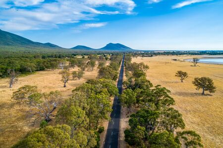 Straight road leading to a mountain among fields and trees in Australia - aerial view 版權商用圖片