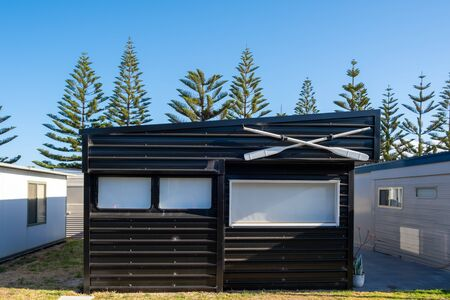 Black holiday cabin decorated with white paddles at a caravan park in Australia 版權商用圖片