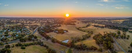 Sun touching the horizon at sunset over Australian outback - wide aerial panorama 版權商用圖片