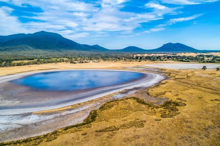 Aerial view of clouds reflecting in a small lake and Grampians mountains in Australia 版權商用圖片 - 138380309