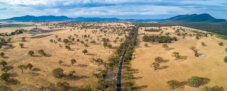 Aerial panorama of Australian outback and rural road with mountains