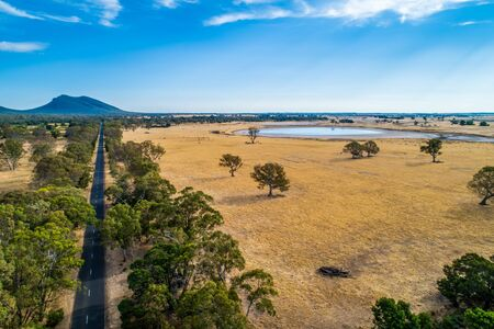 Straight rural highway leading to a mountain among fields and trees in Australia 版權商用圖片