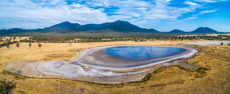 Clouds reflecting in a small lake and Grampians mountains in Australia - aerial panoramic landscape