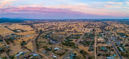 Aerial panoramic landscape of rural road passing through Australian countryside and small settlement at sunset 版權商用圖片