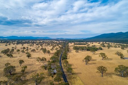 Road leading towards mountains of the Grampians in Victoria, Australia - aerial view