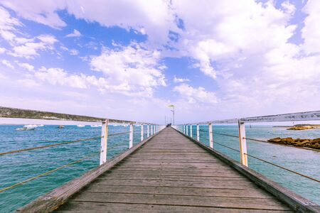 Low angle view of long wooden pier in diminishing perspective under beautiful sky