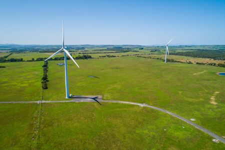 Two wind turbines among green grazelands in the countryside - aerial landscape