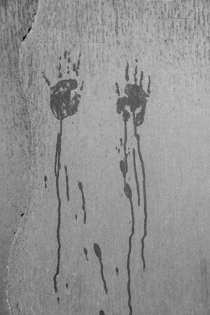 Scary blood dripping hand marks on a wall in black and white Foto de archivo