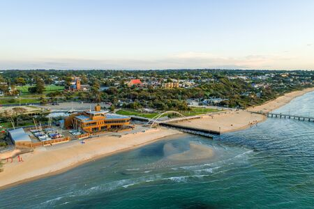 Aerial view of Frankston Yacht Club and footbridge over Kananook creek at the foreshore at sunset.