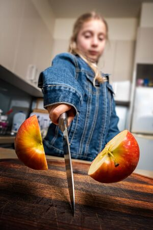 Caucasian girl cutting red apple in half at home in the kitchen. Shallow focus.