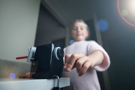 Young girl using pencil sharpener at home Banco de Imagens - 147329704