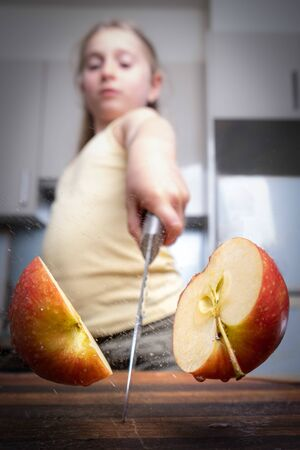 Girl cutting a wet apple in half in the kitchen with shallow focus