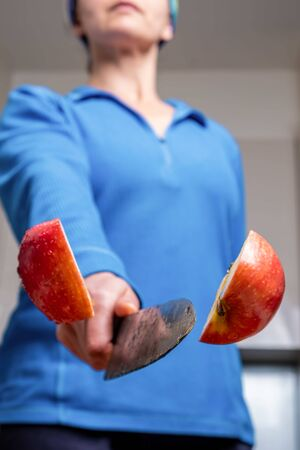 Extreme closeup of woman cutting apple in half mid air with shallow focus