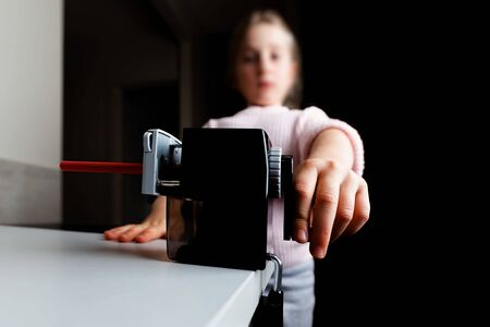 Wide angle closeup of girl hand sharpening red pencil with shallow focus Banco de Imagens - 147329708