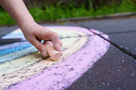 Closeup of child hand drawing rainbow using colorful chalk Banco de Imagens - 147329712
