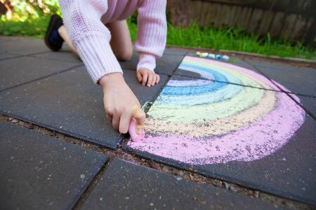 Wide angle view of girl drawing rainbow with shallow focus Banco de Imagens