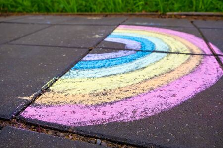 Chalk drawing of rainbow on pavement with shallow focus