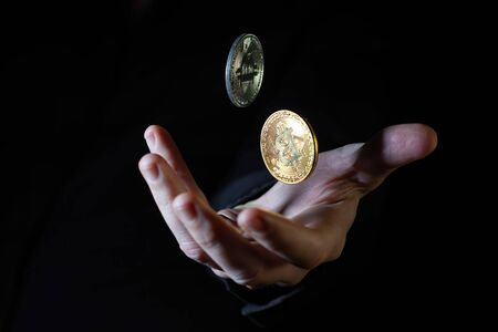 Male hand throwing two bitcoins up in the air on black background - closeup Banco de Imagens - 147329804