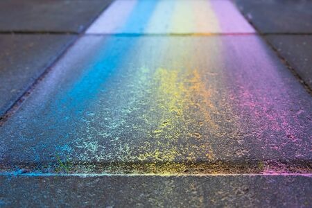Perspective view of colorful rainbow drawing with chalk on pavement with shallow focus Banco de Imagens