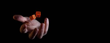 Two orange dice cubes thrown in the air above caucasian male hand against black background - narrow banner with copy space Banco de Imagens - 146506523