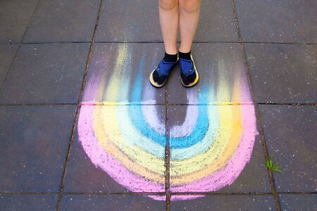 Child feet standing on chalk drawin rainbow