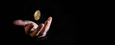 Hand throwing golden bitcoin in the air on black background - narrow banner with copy space Banco de Imagens - 146507823