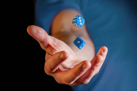 Caucasian male hand throwing blue dice cubes in the air - closeup with shallow focus Banco de Imagens