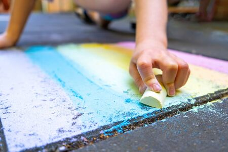 Girl drawing rainbow with chalk on pavement Banco de Imagens