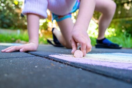 Young caucasian girl drawing rainbow with chalk on floor with shallow focus Standard-Bild