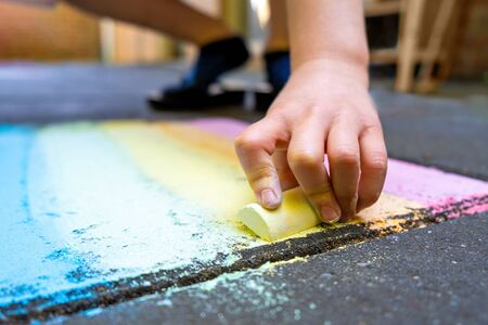Child drawing rainbow with chalk on pavement with shallow focus Banco de Imagens - 147329849