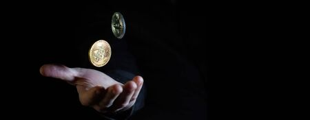 Caucasian male hand throwing two bitcoins in the air against black background - narrow banner with copy space