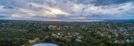 Aerial panorama of Mornington Peninsula on a cloudy day at sunset. Suburban area with trees and Port Phillip Bay