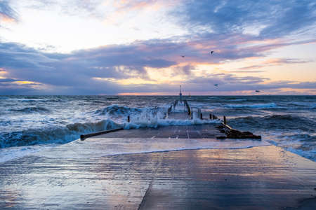 Stormy waves crushing and splashiing over pier at beautiful sunset in Australia Stockfoto