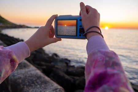 Child hands taking photo of sunset over sea Stockfoto
