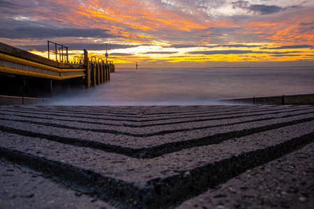 Low angle view of boat ramp at vivid glowing sunset in Australia Standard-Bild