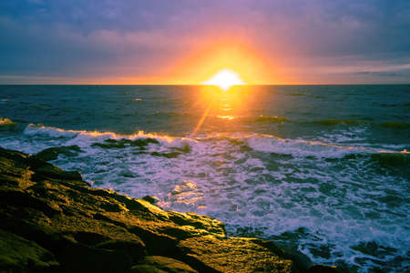 Sunset with sun flare over sea and rocks with waves