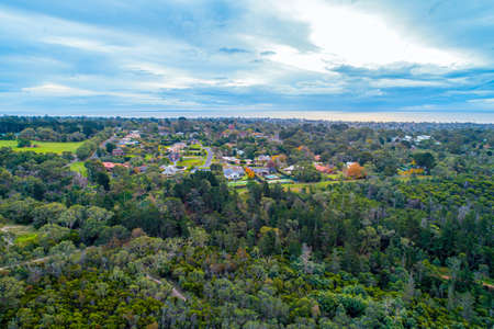 Aerial view of houses surrounded by trees near ocean coastline in Melbourne, Australia Standard-Bild