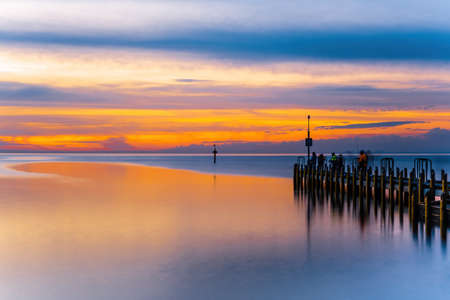 Vivid glowing orange sunset over ocean and boat jetty - long exposure seascape
