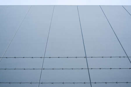 Looking up at barbed wire against concrete wall with copy space 版權商用圖片