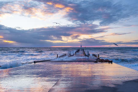 Beautiful sunset with powerful crushing waves and wooden pier in Austrlaia Stockfoto