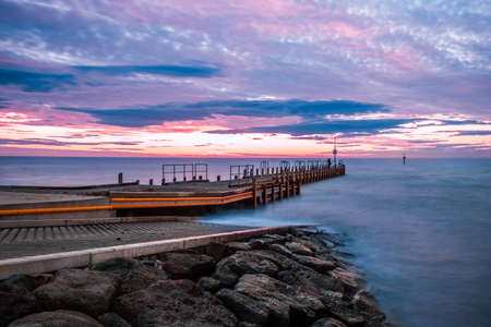 Scenic sunset over ocean and boat jetty - long exposure landscape