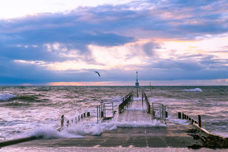 Beautiful sunset over foreshore with big waves and boat jetty Stockfoto