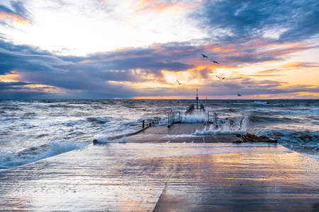Storm waves crushing on a pier with flying seagulls at sunset in Melbourne, Australia