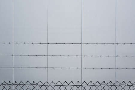 Barbed wire over mesh fence against concrete wall with copy space