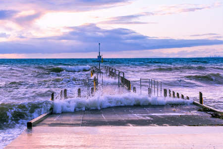 Waves splashing over boat jetty on ocean shore in Australia at sunset