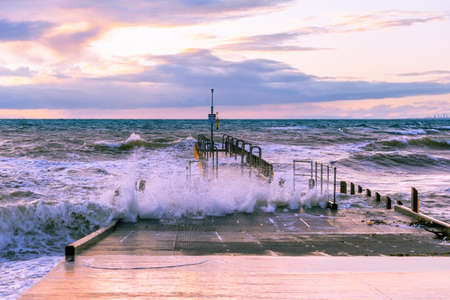 Boat jetty hit by strong waves at sunset on ocean shore Stockfoto