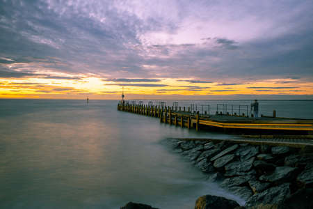 Long exposure of silky smooth ocean water and pier at sunset with photographer silhouette and tripod Stockfoto