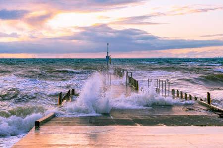 Large wave splashes protruding through boat jetty on ocean coastline at sunset Stockfoto
